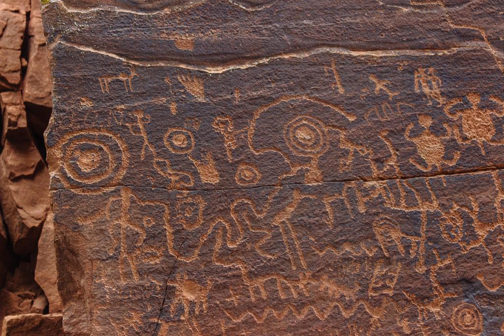 Light orange human animal and geometric petroglyphs on a dark brown rock face