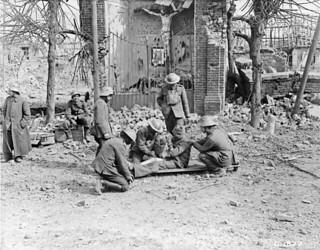 A stretcher bearer and German prisoner assist as dressings are applied to wounded Canadian... / Un porteur de civière et un prisonnier allemand offrent leur aide pendant que des pansements sont appliqués sur un Canadien blessé...