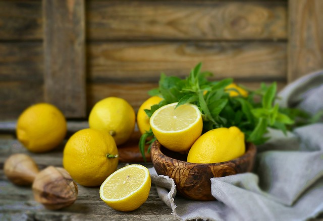 juicy and ripe organic lemons in a and fresh mint on a wooden background