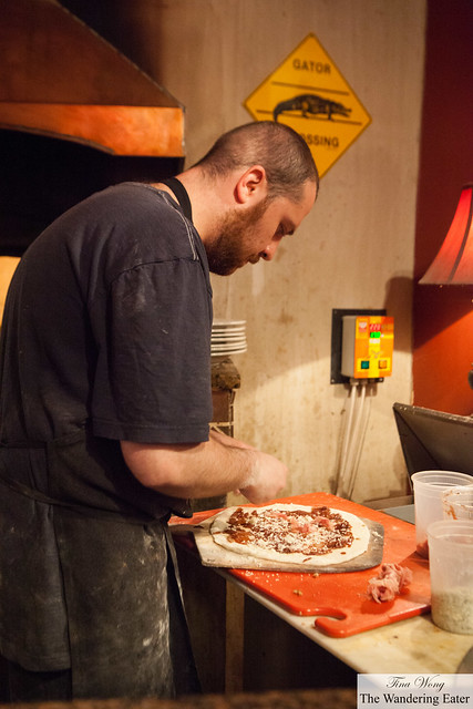 Making The House Specialty Pizza that will go into the wood burning oven