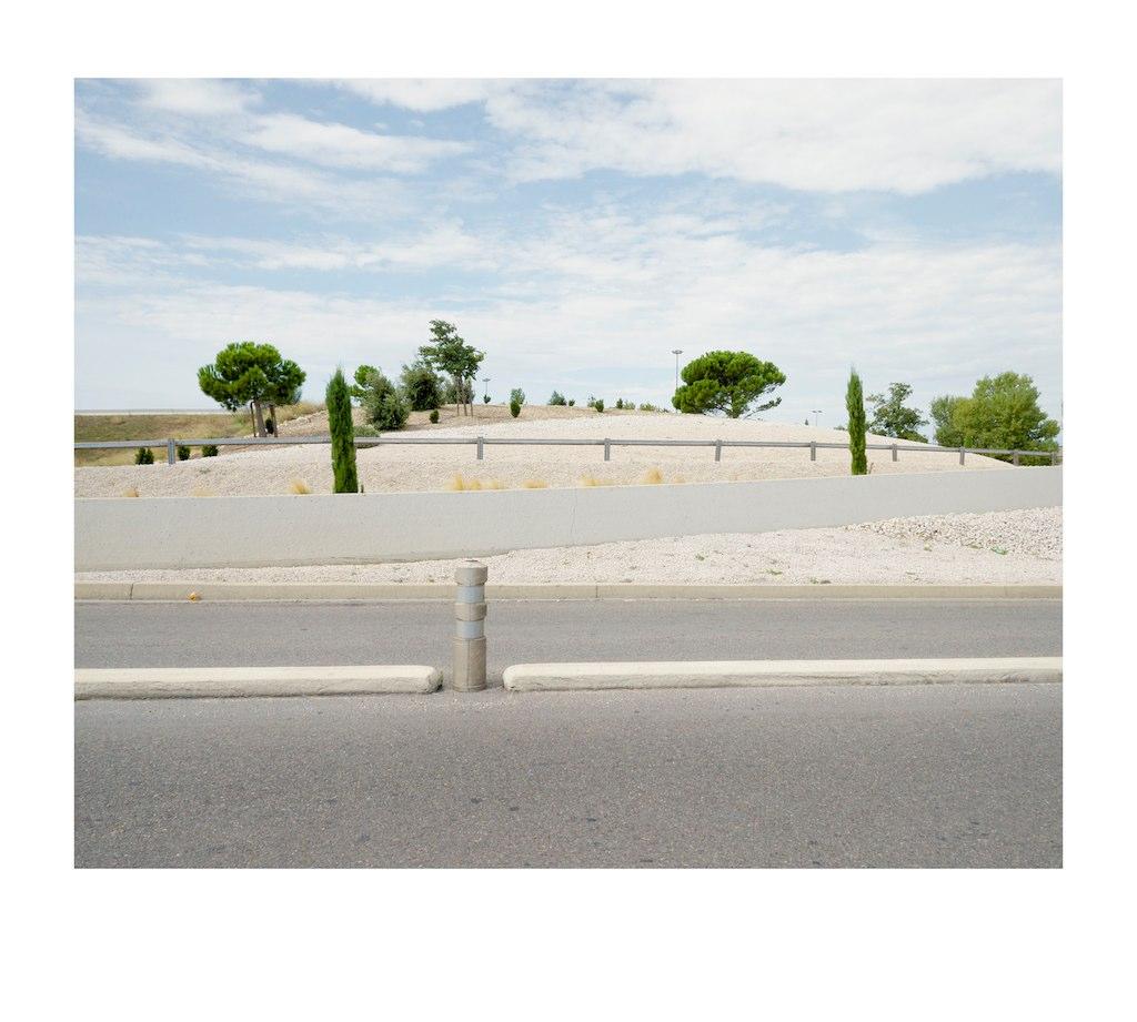 Road, bollard, bank and trees.