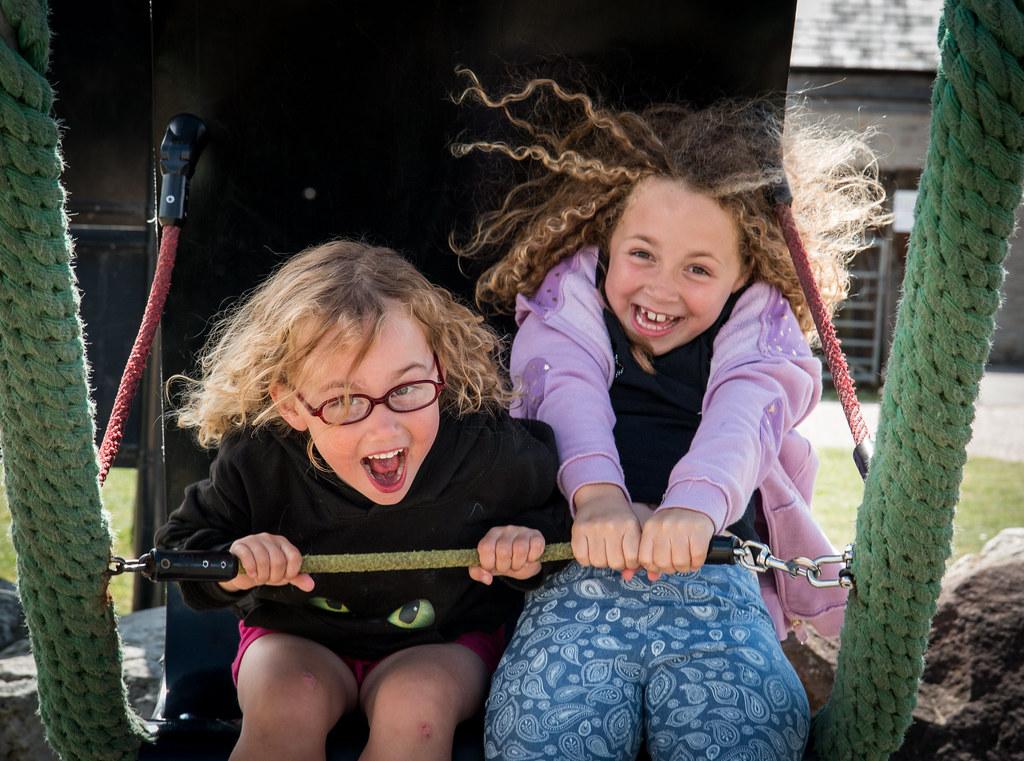 2 petites filles qui font de la balançoire