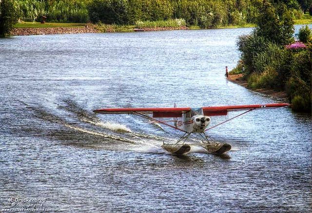 A Piper Super Cub on floats lands on the Chena River in Fairbanks
