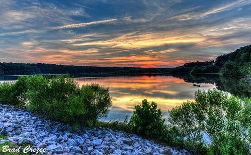 nikon d800 sigma1224 lakewheeler raleigh northcarolina sunset red orange yellow sky clouds trees rocks blue bradcrezee