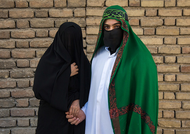 Portrait of iranian shiite muslim couple with their faces hidden by a veil mourning imam hussein on tasua during the chehel manbar ceremony one day before ashura, Lorestan province, Khorramabad, Iran