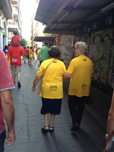 Two older yellow t-shirted demonstrators in Gràcia after the demonstration | by Liz Castro