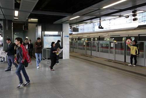 Train doors closing, and MTR staff hold up 'STOP' signs to passengers at Ngau Tau Kok