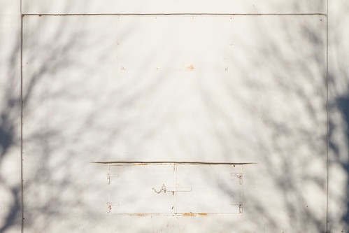 wall with closed lid in high light complete with shadows from two trees | by Thomas (pib)