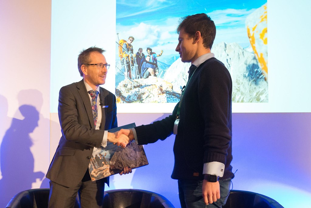 Competition winner Sarunas stands on stage at the Erasmus+ Effect Annual Conference to collect his prize