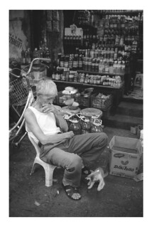 Old man with his cat in front of his sundries kiosk | by kiemchacsu