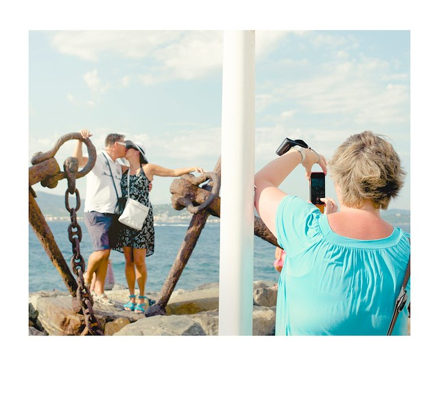 Tourists kissing for photograph.
