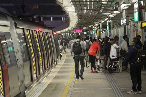 Passengers with bikes depart the train at Kowloon Tong station