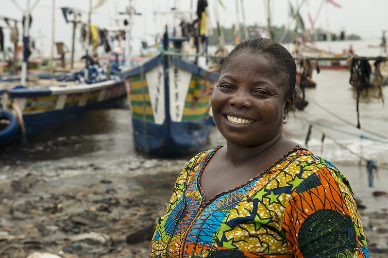 Portrait of Mrs Emelia Abaka-Edu in front of her boat in Axim village, Ghana. Photo by Anna Fawcus.