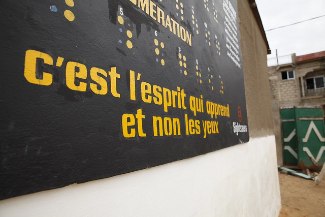 """A Braille-covered mural at the entrance to L'Ecole Malick Diop in Dakar, Senegal, which reads """"It's the mind that learns, not the eyes""""."""