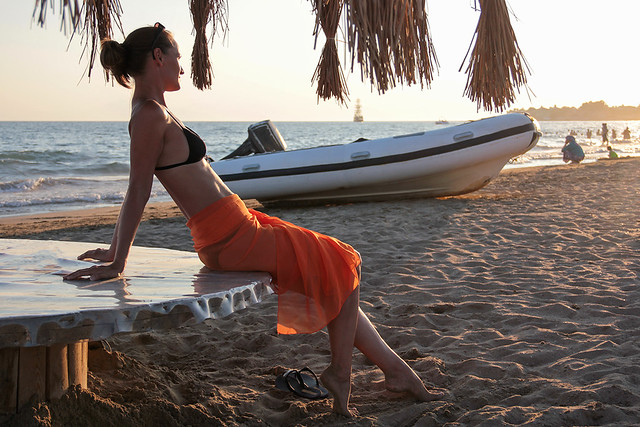 Woman in an orange scarf on the beach 13