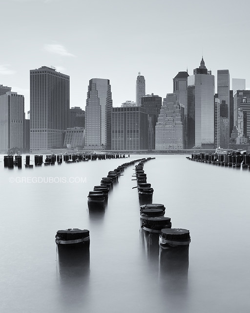 New York City Skyline, Lower Manhattan over East River from Brooklyn Bridge Park with Pilings and Long Exposure Water Blur