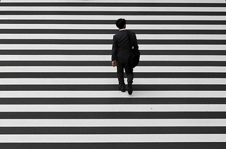 A businessman crosses a road in Tokyo's business district on October 1, 2015. | by Jordi Bernabeu