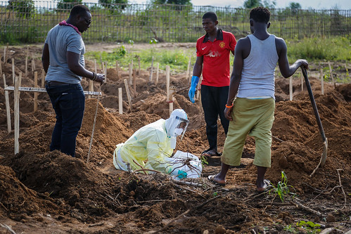 The last burial: Alfred Kelfala from the roving Freetown Ebola burial team carefully lowers the corpse of a small child into its grave | by DFID - UK Department for International Development