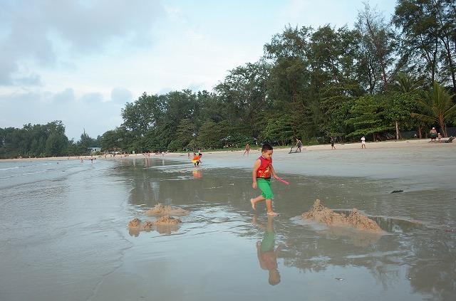 <p>夕暮れ時にビーチで遊ぶ男の子</p>