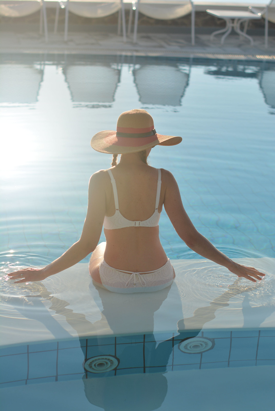 Santorini hotel pool: White bikini, wide-brimmed hat | Not Dressed As Lamb