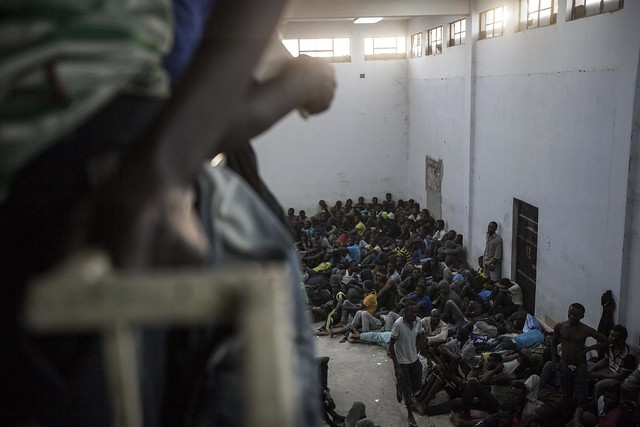 A group of sub-Saharan illegal migrants and refugees are crowded into one section of the Zawiyah Detention Centre, a warehouse-like facility holding as many as 2,000 detainees at any one time, making it the largest of its type on Libyan soil. The centre serves as a distribution facility in the human trafficking supply chain, and from here inmates are resold to other militias on the west coast of Libya. Zawiyah, Libya