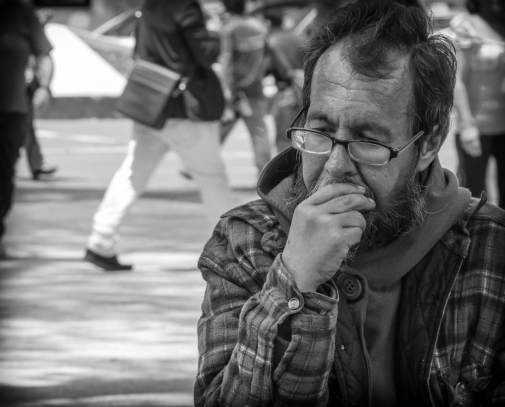 Homeless man ponders while sitting on a bench along Paseo de la Reforma