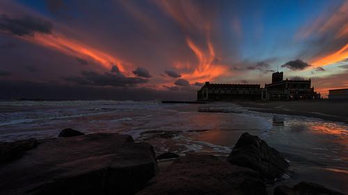 ocean sunset sky reflection water colors landscape us newjersey sand rocks unitedstates dusk asburypark nj shore northbeach conventionhall