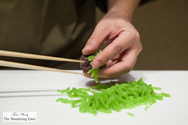 Chef covering the red bean namagashi core with the grass colored bean paste