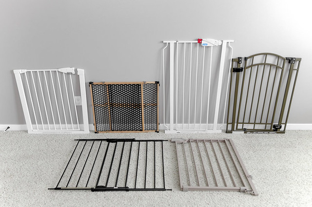 Six baby gates lined up on carpet in living room
