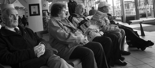 street uk portrait people urban blackandwhite bw woman white man black monochrome face swansea wales person photography reading mono newspaper eyecontact sitting zoom candid cymru streetphotography wideangle olympus sat unposed seated busstation 43 omd zoomlens 14mm mft abertawe em5 1442mm microfourthirds justard justardcom