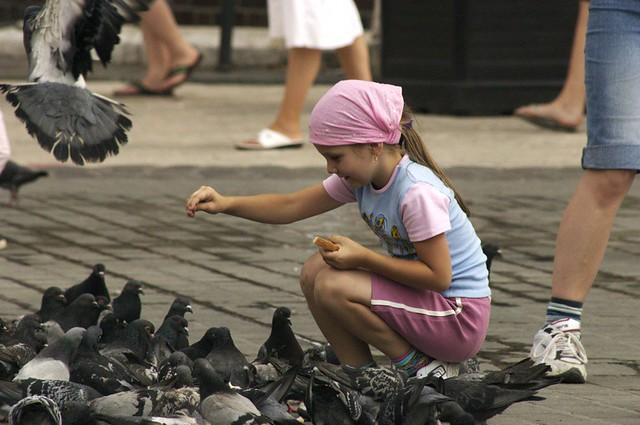 Girl feeding pigeons in the town square - Krakow, Poland, 2006.