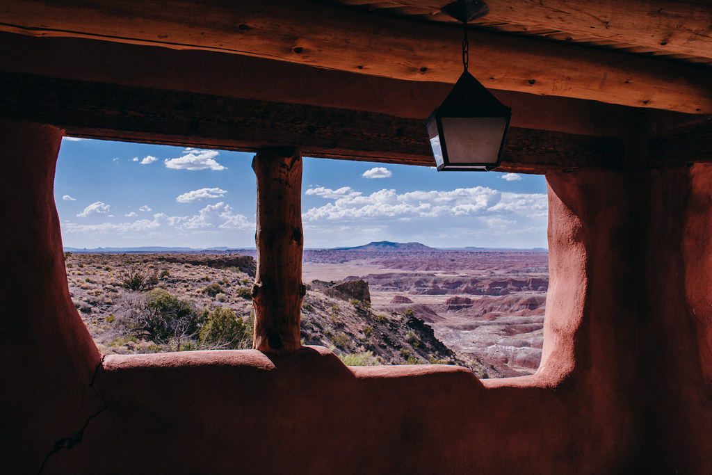 Silhouette of two wooden framed windows with a view of the painted desert and clouds in a blue sky