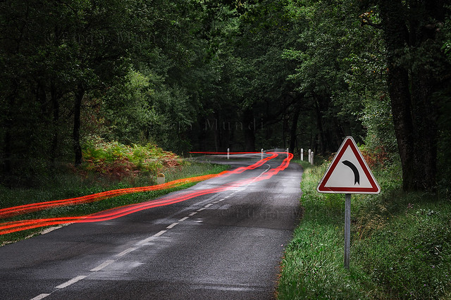 Road warning sign and motion light streak on country road