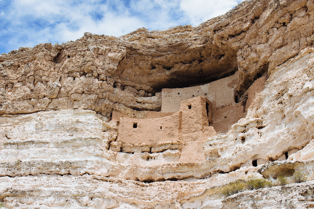 Stone cliff dwellings built into the side of a curving limestone cliff