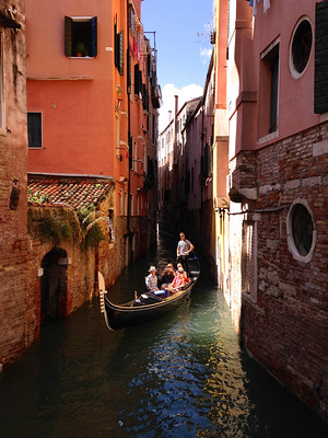A shady canal in Venice with a boat