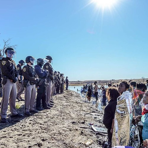 This is America. Right now.  Photo: Rob Wilson, Rob Wilson Photography  #StandWithStandingRock #NoDAPL #WaterIsLife #IndigenousRising #IndigenousUnited #Protector #WaterProtectors #MortonCounty #BLACKSNAKE #Solidarity #StillHere #HonorOurTreaties #Wateris | by eyewashdesign: A. Golden