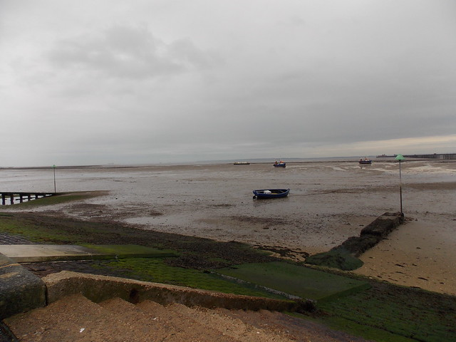 BOATS AT ANCHOR ON THE SAND AS THE SEA OR OCEAN HAS EBBED ON A  DULL WET EVENING  OF SOUTHEND ON SEA  AN EAST COAST HOLIDAY RESORT IN THE COUNTY OF ESSEX ENGLAND 24-10-2015  DSCN0981