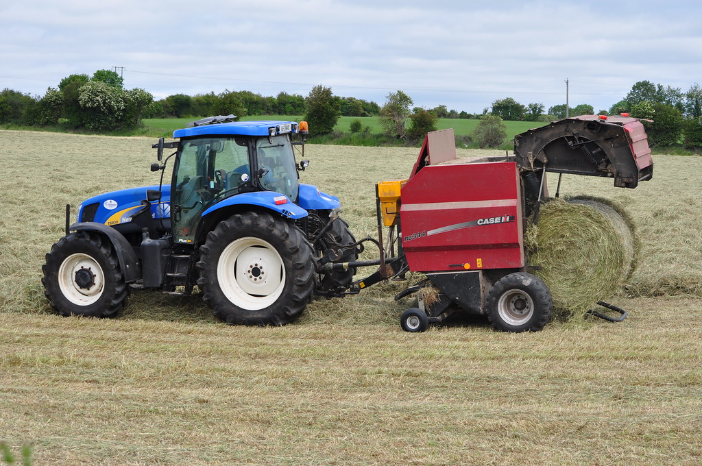 New Holland T6030 Tractor with a Case IH RB334 Round Baler…   Flickr