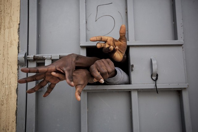 Sub-Saharan illegal migrants and refugees reach through the window of a cell in the Garabuli Detention Centre, pleading for water, cigarettes, food and their release. Garabuli, Libya.