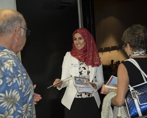 Graduate student Razaz Banoun hands out programs