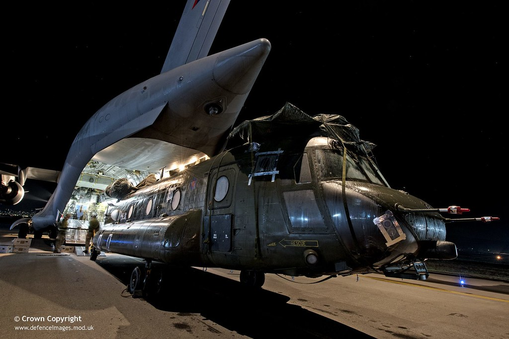 An RAF Chinook helicopter is loaded into a C-17 Globe master.