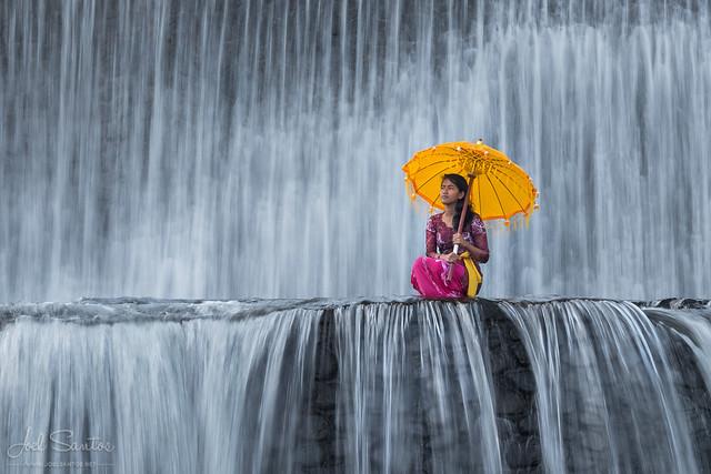 Balinese girl with cerimonial umbrella, Waterfall, Bali, Indonesia