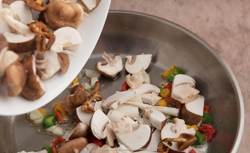 Adding mushrooms to fried chili pepper.