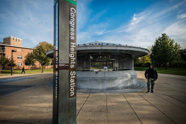 Photo of the Congress Heights Metro station with a man standing next to the covered entrance and an apartment building visible in the distance.