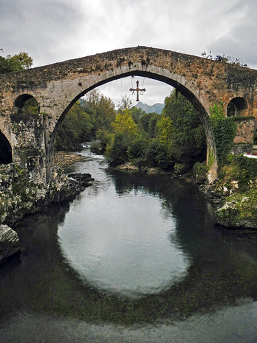 The Roman bridge and cross over the river at Canga de Onis in Northern Spain