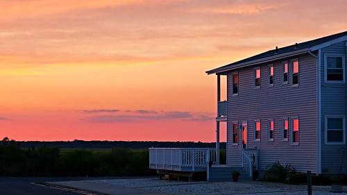 pink windows light sunset sky house clouds reflections horizon deck porch grasslands