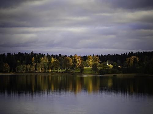 blue autumn trees sky lake reflection green monument nature water yellow clouds outdoor latvia lettland aluksne latvija daba lettonie ezers ainava alūksne