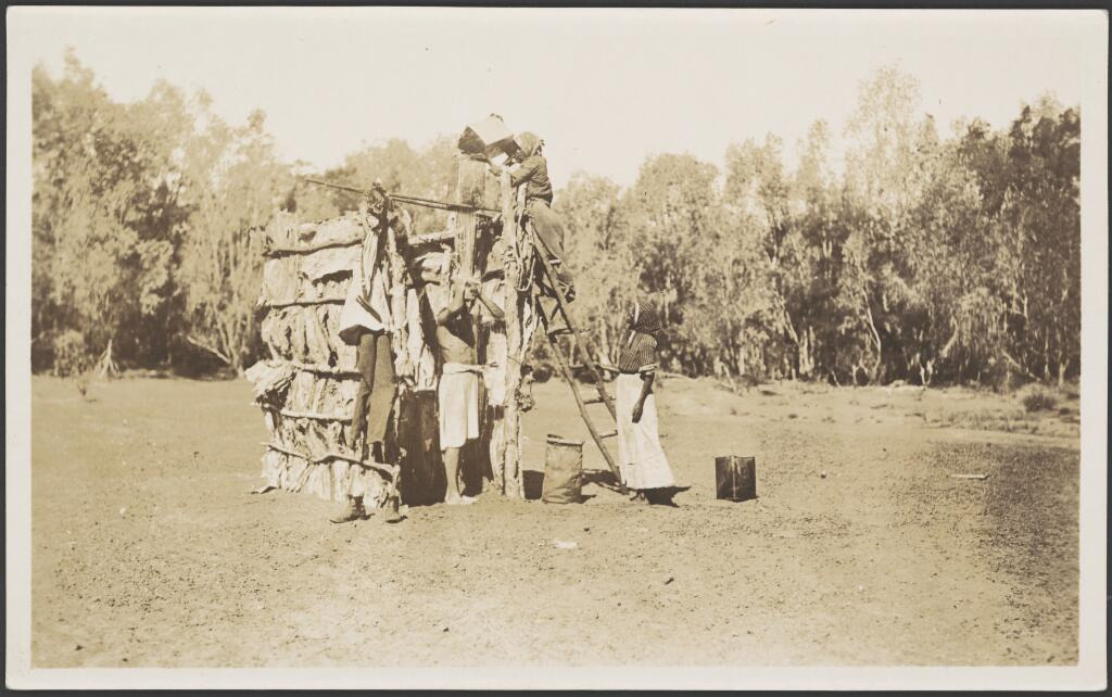 Francis Birtles in a bush shower constructed of timber and paper bark strips, 1914 / Frank Hurley