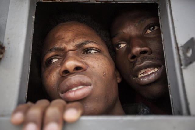 Illegal migrants from sub-Saharan Africa look through the window of a cell in the Garabuli Detention Centre, pleading for water, cigarettes, food and their release. Garabuli, Libya