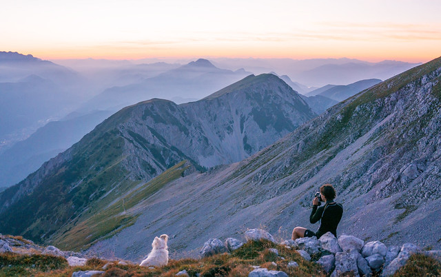Photographer and his dog shooting a sunset in the mountains